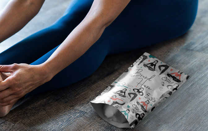 A stand up pouch, custom printed by The Packaging Lab, next to a person stretching.
