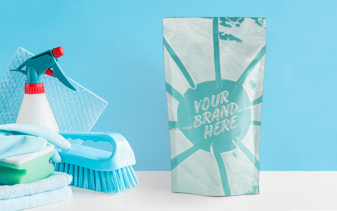 A stand up pouch next to cleaning products, such as brushes and cloths. The Packaging Lab offers packaging printing for businesses that sell household products.